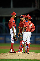 Williamsport Crosscutters pitching coach Hector Berrios (21) talks with relief pitcher Manuel Silva (11) and catcher Rafael Marchan (13) in a mound visit during a game against the Mahoning Valley Scrappers on August 28, 2018 at BB&T Ballpark in Williamsport, Pennsylvania.  Williamsport defeated Mahoning Valley 8-0.  (Mike Janes/Four Seam Images)