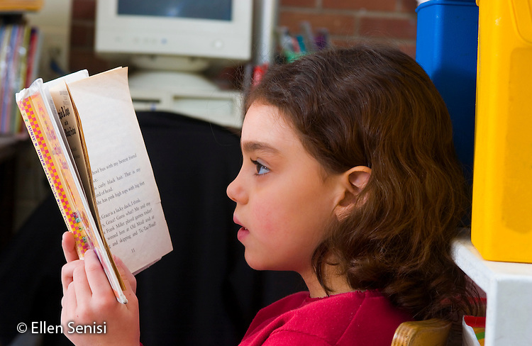 MR/Schenectady, New York.Zoller School- Inclusion classroom (urban, public, elementary school)/ Grade 1    Girl (6, Puerto-Rican-American-Caucasian) reads chapter book at free reading time..MR:Spr1.© Ellen B. Senisi