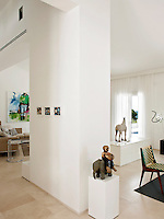 A detail of a white, contemporary living space with a sand-blasted stone floor. The minimal, neutral space provides the perfect backdrop to display the owners impressive collection of artworks such as the figurative piece by Daniel Wagenblast.