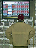Man inspects arrival and departure boards at Columbus International airport. My Final Photo taken  Nov. 24, 2004.<br /> <br /> <br /> Photo Copyright 2004 Gary Gardiner. Not to be used without written permission detailing exact usage. Photos from Gary Gardiner, may not be redistributed, resold, or displayed by any publication or person without written permission. Photo is copyright Gary Gardiner who owns all usage rights to the image. Low resolution photo with watermark.
