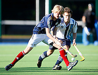 Wes Jackson (L) of East Grinstead shields the ball from Toby Roche during the England Hockey League Mens Premier Division game between Hampstead & Westminster against East Grinstead at The Paddington Recreation Ground, Maida Vale on Sun Oct 10, 2010
