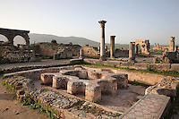 Atrium of the House of the Labours of Hercules, 2nd century AD, named for a mosaic of Hercules' 12 trials. The house is palatial with 41 rooms covering 2000 sq m. In the distance is the Triumphal Arch of Caracalla, 217 AD, Volubilis, Northern Morocco. Volubilis was founded in the 3rd century BC by the Phoenicians and was a Roman settlement from the 1st century AD. Volubilis was a thriving Roman olive growing town until 280 AD and was settled until the 11th century. The buildings were largely destroyed by an earthquake in the 18th century and have since been excavated and partly restored. Volubilis was listed as a UNESCO World Heritage Site in 1997. Picture by Manuel Cohen
