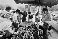 Paris, August 1977. Flea Market. August in Paris is a noveable feast. While millions of residents are leaving for their favourite resorts, thousands of foreign tourists are flocking to the French Capital. Nevertheless, genuine Parisians, old and young alike, stay in Paris and mantain the tradition charm.