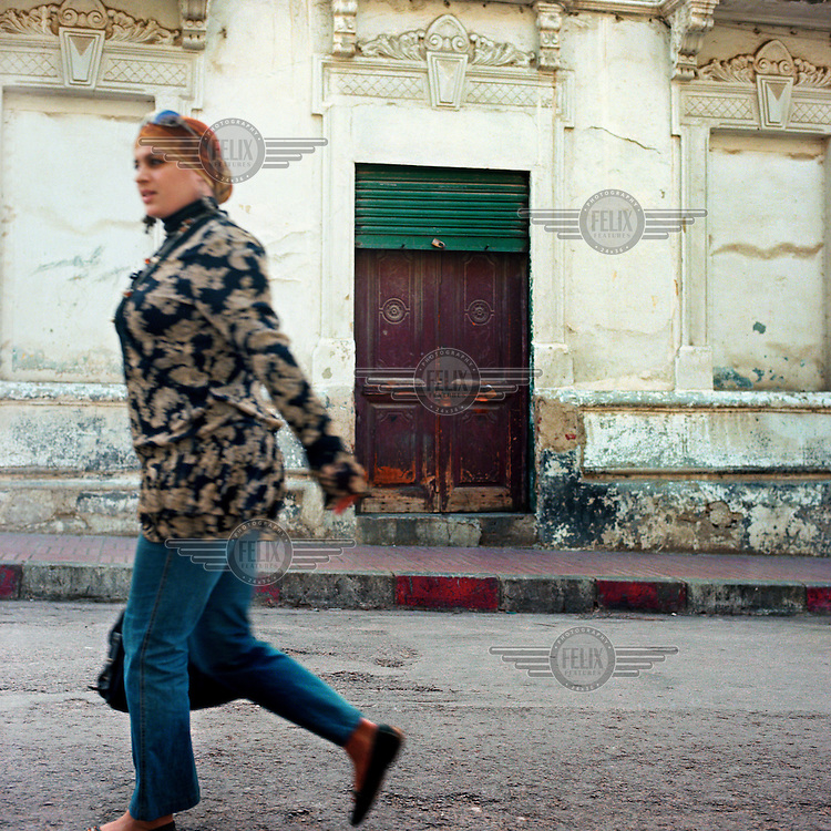 A woman walks past an old building in Casablanca.