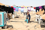 DOMIZ, IRAQ: A father and daughter walk past drying laundry in the Domiz refugee camp...Over 7,000 Syrian Kurds have fled the violence in Syria and are living in the Domiz refugee camp in the semi-autonomous region of Iraqi Kurdistan...Photo by Ari Jalal/Metrography