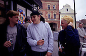 Prague, Czech Republic. Three young adults drinking club soda from bottles and laughing on the street.