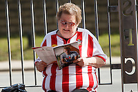 A fan reads the programme before the Barclays Premier League match between Southampton v Swansea City played at St Mary's Stadium, Southampton