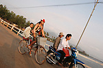 CAMBODIA  -  APRIL 3, 2005:  Two young girls riding a bicycle cross the Kampot River along with a man and a woman on a moped on April, 3, 2005 in Kampot, Cambodia. (PHOTOGRAPH BY MICHAEL NAGLE).