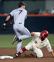 Virginia infielder Branden Cogswell (7) throws to first after tagging out Arkansas outfielder Tyler Spoon (8) at second base in the second inning during an NCAA college baseball regional tournament game in Charlottesville, VA., Friday, June 1, 2014. (Photo/Andrew Shurtleff)