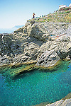 A boy about to jump off of a rock into the blue sea at Manarola, in the Cinque Terre, Italy.