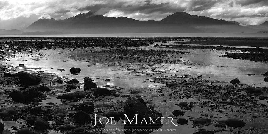 Rocks and dramatic clouds during low tide at Kachemac Bay, Homer, Alaska