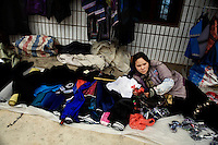 Ethnic minority women display goods for sale on the ground on market day in Pangzhihua Village, Yuanyang County, Yunnan Province, China.