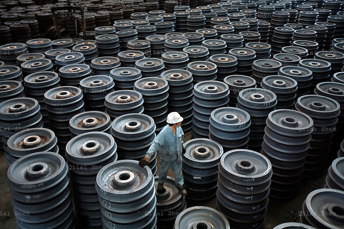 QS060410Maanshan098 A worker inspects stacks of train wheels at the Wheel and Tyre Plant of Ma Steel (Maanshan Iron & Steel Co.) in Maanshan, Anhui Province, China on Monday 10 April 2006. The plant is the largest producer of train wheels in China.