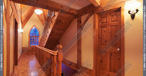 Timber frame cottage style Canadian country house hall interior with a wooden staircase and a gothic arch cathedral window, Muskoka, Ontario, Canada