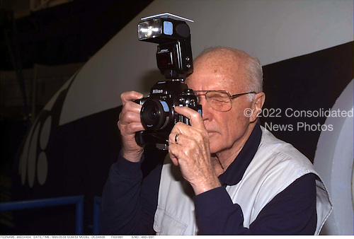 United States Senator John H. Glenn Jr. (Democrat of Ohio) takes a picture with a 35mm camera while standing in front of one of the Shuttle mockup/training facilities at the Johnson Space Center (JSC) in Houston, Texas on May 9, 1998. Glenn, the first American to orbit Earth (over 36 years ago), is assigned to fly as a payload specialist on STS95, aboard the Space Shuttle Discovery, later in 1998, stands in front of the full fuselage trainer (FFT) in the systems integration facility. .Credit: NASA via CNP