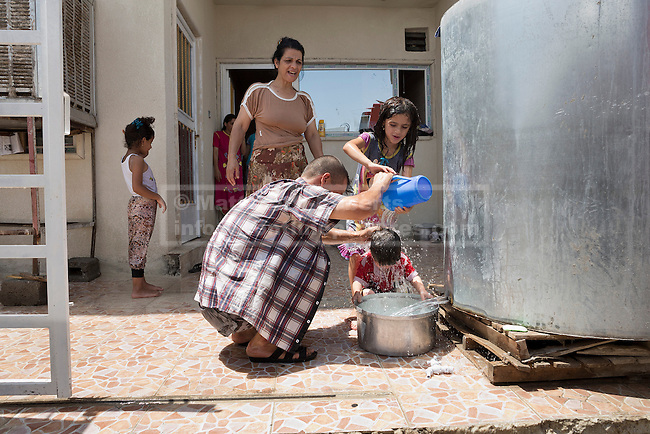 Christian refugee Ra'id Samir Kamal (45) washes his youngest daughter after Kurdish Zeravani soldiers distributed fresh supplies of drinking water to refugee families living in partially built houses in Hamdaniyah, Iraq.