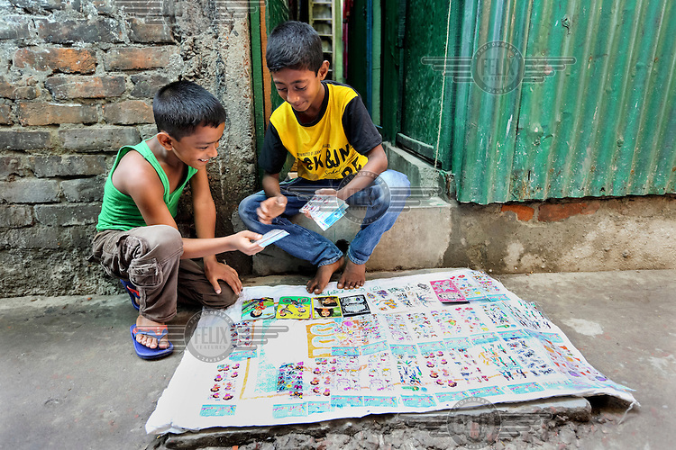 Siam selling stickers to local children in front of his family's house.
