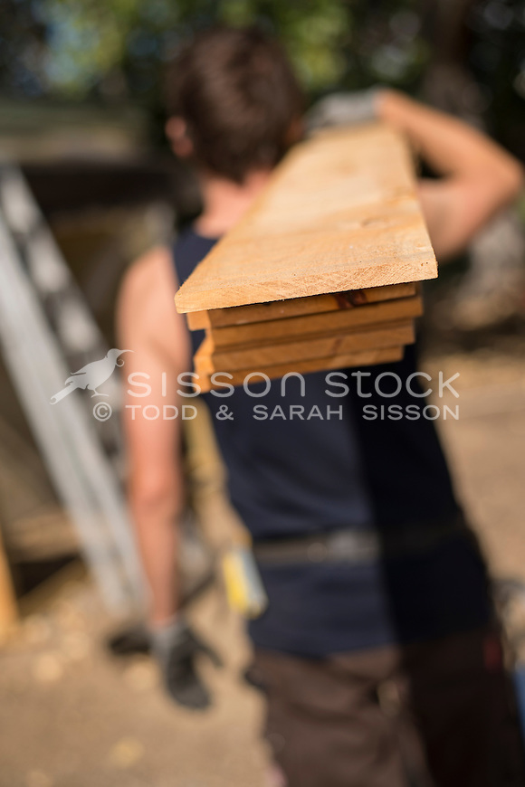 Home handyman wearing safety glasses and carrying wood while working outside on a home renovation project, New Zealand- stock photo, canvas, fine art print