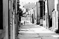 file photo circa 1867 -  Montreal,  Quebec , Canada  - kids play under clothes line in a Montreal back alley