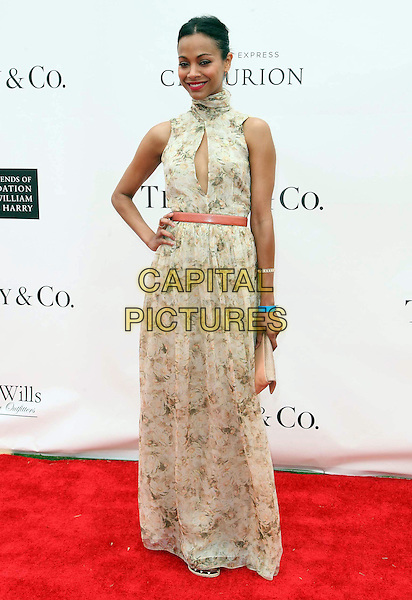 Zoe Saldana.Audi At The Foundation Polo Challenge held at the Santa Barbara Polo & Racquet Club, Santa Barbara, California, USA, 9th July 2011..full length green beige print floral long maxi dress belt cut out sleeveless clutch bag  high neck green  hand on hip .CAP/ADM/KB.©Kevan Brooks/AdMedia/Capital Pictures.