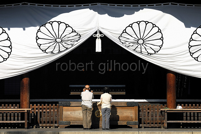 A couple bows during prayer at the main hall of Yasukuni Shrine in Tokyo, Japan.very year on August 15, the day Japan officially surrendered in WWII, tens of thousands of Japanese visit the controversial shrine to pay their respects to the 2.46 million war dead enshrined there, the majority of which are soldiers and others killed in WWII and including 14 Class A convicted war criminals, such as Japan's war-time prime minister Hideki Tojo. Each year speculation escalates as to whether the country's political leaders will visit the shrine, the last to do so being Junichiro Koizumi in 2005. Nationalism in Japan is reportedly on the rise, while sentiment against the nation by countries that suffered from Japan's wartime brutality, such as China, has been further aggravated by Japan's insistence on glossing over its wartime atrocities in school text books...Photographer:Robert Gilhooly....Photographer:Robert Gilhooly