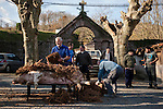 A professional butcher (in blue overalls) and some more men  cover the dead pig with dry bracken to be burnt in traditional way pig slaughtering.  Doneztebe (Basque Country). December 08. 2016. The slaughter traditionally takes place in the autum and early winter and the work often is done in the open. (Gari Garaialde / Bostok Photo)