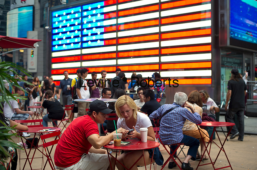 Tourists in front of an electronic American Flag which adorns the sides of the Armed Forces Recruitment booth on Military Island in Times Square, seen on Sunday, September 2, 2012. (© Frances M. Roberts)