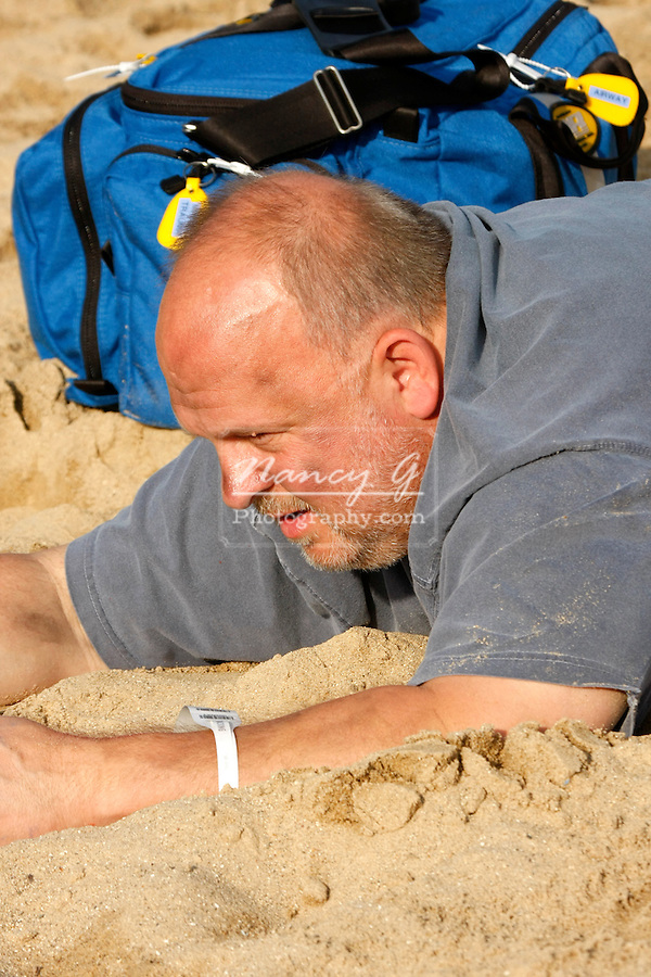 A male mass casualty victim laying in the sand on a beach with ems bag