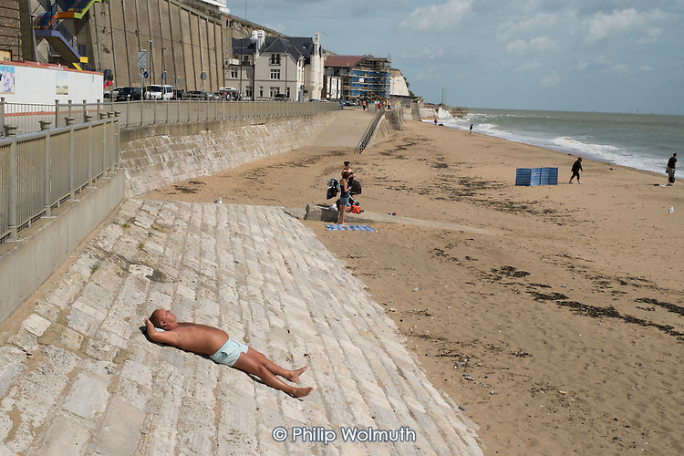 A solitary sun-bather on the beach in high season in Ramsgate, one of the five most deprived seaside towns in the UK.