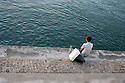 A man sits on the Rhone river bank with a bottle of water and bag of Van Gogh Foundation, Arles July 9, 2016
