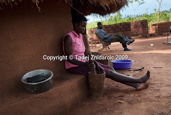 Woman pounds millet in her compound, Acoyo village, Koro Subcounty, Gulu District. After returning home from camps for internally displaced persons (IDPs), people in northern Uganda are rebuilding their houses, starting to cultivate the land and engage in trading.
