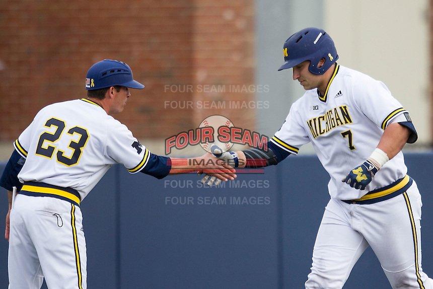 Michigan Wolverines catcher Harrison Wenson (7) is greeted by third base coach Nick Schnabel (23) after hitting a home run against the Toledo Rockets on April 20, 2016 at Ray Fisher Stadium in Ann Arbor, Michigan. Michigan defeated Bowling Green 2-1. (Andrew Woolley/Four Seam Images)