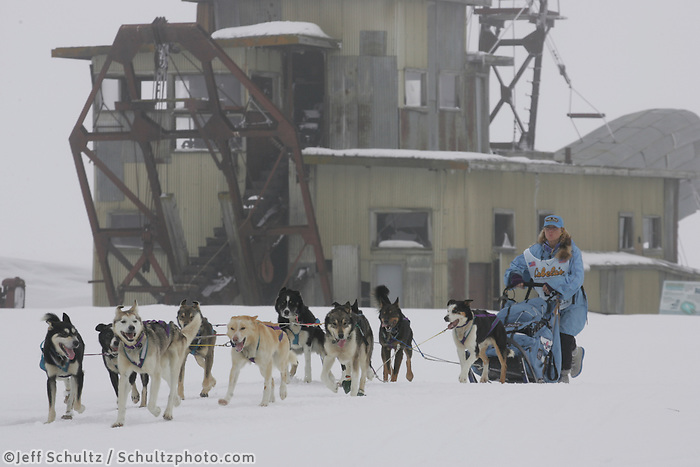Dee Dee Jonrowe passes Swanberg's gold dredge on the trail nearing Nome in foggy conditions.    End of the  2005 Iditarod Trail Sled Dog Race.