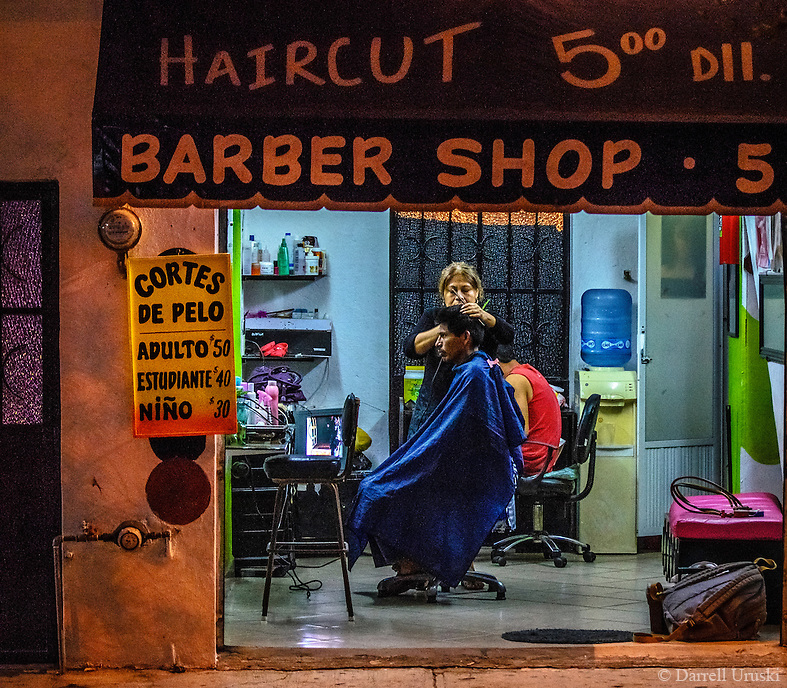 Urban Street Photography. Night Scene of a barber shop in Mexico. Haircuts $5.00 prominently advertised on the wall and awning of the building entice local men to get a haircut. The busy barber is hard at work cutting his hair.
