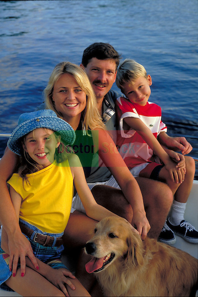portrait of smiling family at beach with pet dog