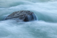Pure glacial waters flow over a rock in central Bhutan.