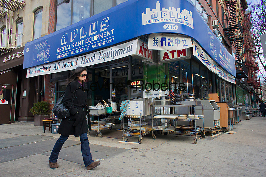 A woman walks past a restaurant supply seller on the changing Bowery in New York on Saturday, January 28, 2012. (© Richard B. Levine)
