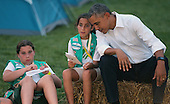 United States President Barack Obama sits next to Girl Scouts Daphnye Shell (C), 9, of Peggs, Oklahoma, and Charlotte Sims (L), 9, during a campout on the South Lawn of the White House June 30, 2015 in Washington, DC. The president and first lady Michelle Obama hosted the event as part of the first lady's Let's Move! Outside initiative and for Girl Scouts to earn the new Girls' Choice Outdoor badge.<br /> Credit: Chip Somodevilla / Pool via CNP