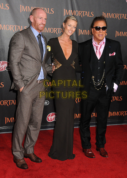 guest, Anastassija Makarenko & Mickey Rourke .The World Premiere of 'Immortals' held at The Nokia Theater Live in Los Angeles, California, USA..November 7th, 2011.full length brown low cut neckline cleavage gold sequins sequined clutch bag black suit waistcoat pink shirt sunglasses shades couple grey gray blue .CAP/ADM/BP.©Byron Purvis/AdMedia/Capital Pictures.