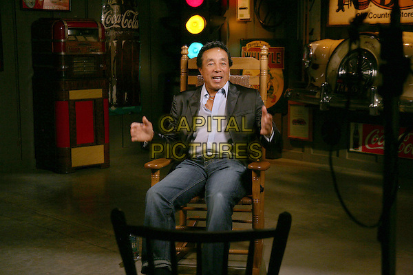 SMOKEY ROBINSON.Smokey Robinson during a visit to the Cracker Barrel Old Country Store corporate offices in Lebanon, TN, USA..October 13th, 2010.full length jeans denim black jacket chair hands mouth open white shirt sitting.CAP/ADM/RR.©Randi Radcliff/AdMedia/Capital Pictures.