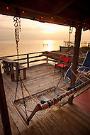 A porch swing hangs from the back porch of a coastal cottage in Nags Head, NC