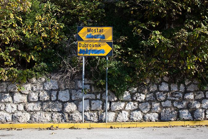 Ein zweisprachiges Straßenschild steht an der Haupstraße, der Jadranska Magistrala in Neum, Bosnien. Die kyrillische Schrift ist übermalt. In Bosnien Herzegowina müssen Straßenschilder zweisprachig sein, da das Land zu 51 Prozent aus der bosnische kroatischen Föderation (lateinische Schrift) und zu 49 Prozent aus der Republica Srpska (kyrillische Schrift) besteht. Das Übermalen der jeweiligen Schrift des Anderen ist ein Symbol dafür, dass die Kultur der Nachbarn nicht anerkannt wird. /<br />Der kleine Ort Neum liegt in Bosnien-Herzegovina und bildet den einzigen Zugang zum Meer des Balkanlandes. Auf einer Länge von 9 km durchschneidet der Ort das kroatische Staatsgebiet (Neum-Korridor) Seit dem EU-Beitritt Kroatiens ist Neum auf beiden Seiten von EU-Außengrenzen eingeschlossen. / The small city of Neum in Bosnia and Herzegovina is the only place in Bosnia, where the country has access to the adriatic sea. Over a length of 9 kilometers the area cuts Croatian territory in two pieces. Since Croatia became part of the European Union, the city of Neum is enclosed between two EU-boarders.