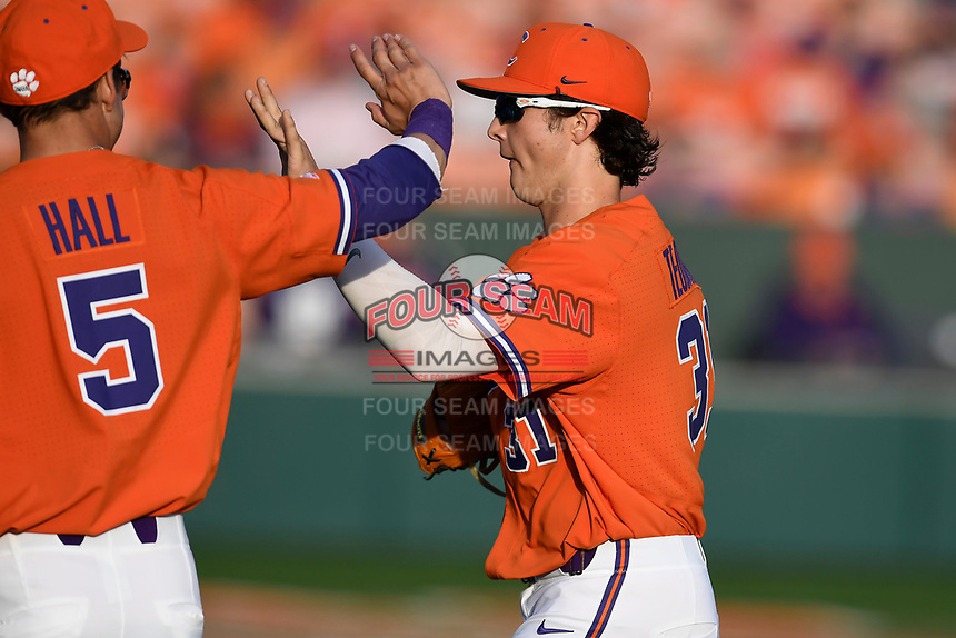 Center fielder Bryce Teodosio (31) of the Clemson Tigers is congratulated ny Ryan Hall after an inning-ending catch in a game against the William and Mary Tribe on February 16, 2018, at Doug Kingsmore Stadium in Clemson, South Carolina. Clemson won, 5-4 in 10 innings. (Tom Priddy/Four Seam Images)