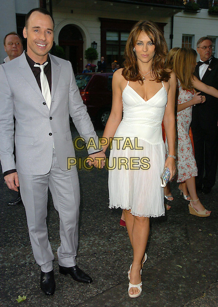 DAVID FURNISH & ELIZABETH HURLEY.Arrivals - The Glamour Magazine 3rd Annual Women Of The Year Awards, Berkeley Square, London, England, .June 6th 2006..full length liz white dress shoes holding hands.Ref: CAN.www.capitalpictures.com.sales@capitalpictures.com.©Can Nguyen/Capital Pictures