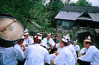 ROMANIA / Maramures / Budesti / 02.09.2006..A traditional wedding procession in one of the most traditional villages in Europe. After gathering at the bride's home, young men walk through the village with a band singing folk songs and offering toasts of homemade plum brandy to villagers on their way to the church for the wedding ceremony...© Davin Ellicson / Anzenberger