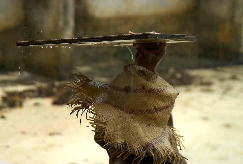 CHUUK GENERIC, FISHERMAN DURING A TROPICAL RAINSHOWER,CHUUK, MICRONESIA, PACIFIC
