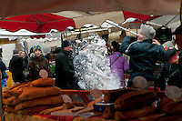 A stallholder scrapes snow off the roof of his bakery stall at the weekly Wednesday morning market, Le Grand Bornand, France, 15 February 2012.
