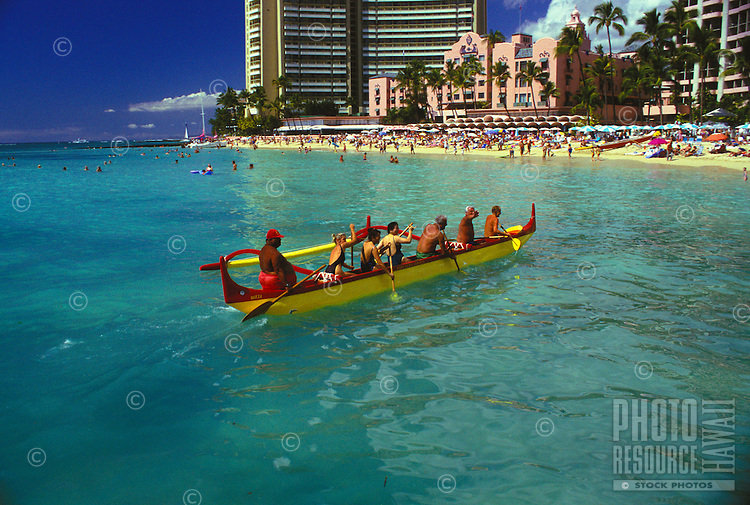 Tourists paddling an outrigger canoe off famous waikiki beach, with the Royal Hawaiian hotel in rear, Oahu