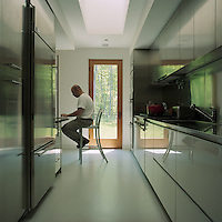 A door at the end of the stainless-steel galley kitchen leads directly to the garden and woodland beyond
