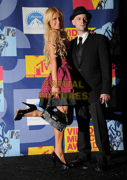 PARIS HILTON & BENJI MADDEN.The 2008 MTV Video Music Awards held at Paramount Studios in Hollywood, California, USA..September 7th, 2008.Pressroom VMA Vmas full length pink purple dress suit jacket hat tattoo couple necklace strapless bag purse shoes leg foot up.CAP/DVS.©Debbie VanStory/Capital Pictures.